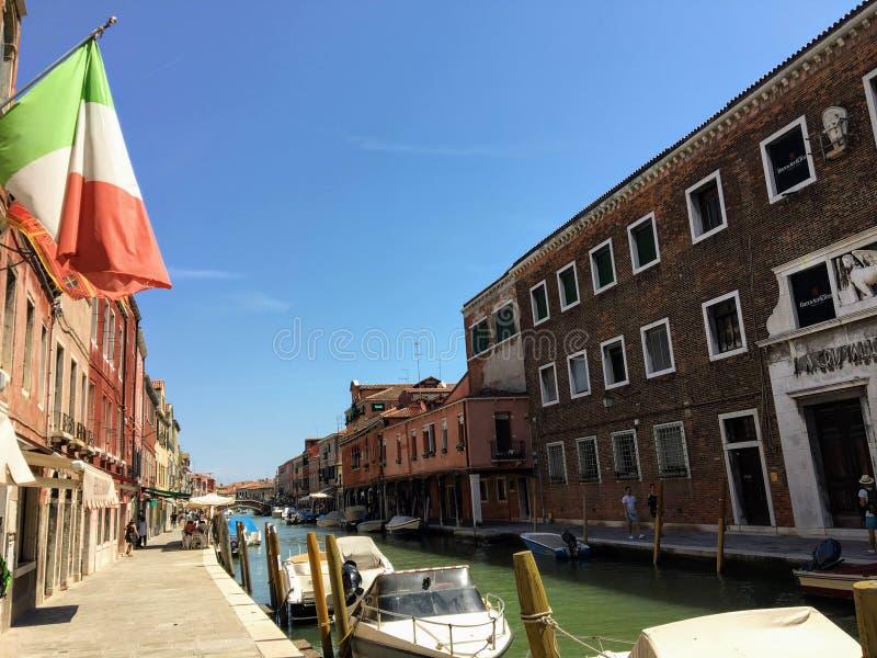 Piękny widok patrzeje w dół ruchliwie kanał w Murano, Włochy Łodzie jadą w dół kanał i turyści odwiedzają sklepy zdjęcia royalty free