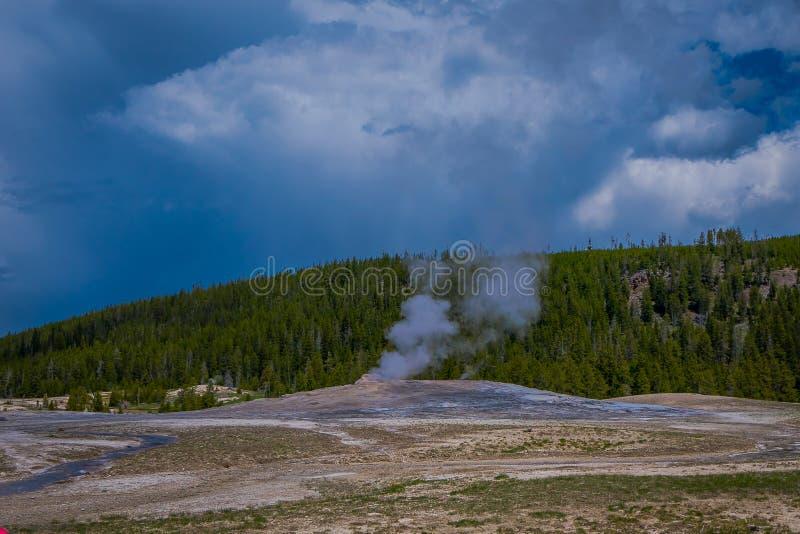 Piękny widok stary wierny gejzeru basen lokalizować w Yellowstone parku narodowym, otaczającym opary z zielenią fotografia stock