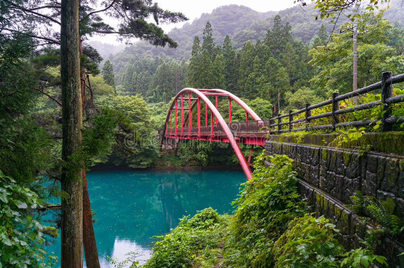 Piękny wieś krajobraz z czerwień łuku mostem nad błękitnym l obrazy stock
