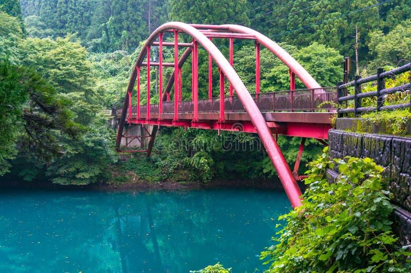 Piękny wiejski krajobraz z czerwień łuku mostem nad błękitnym jeziorem obraz royalty free