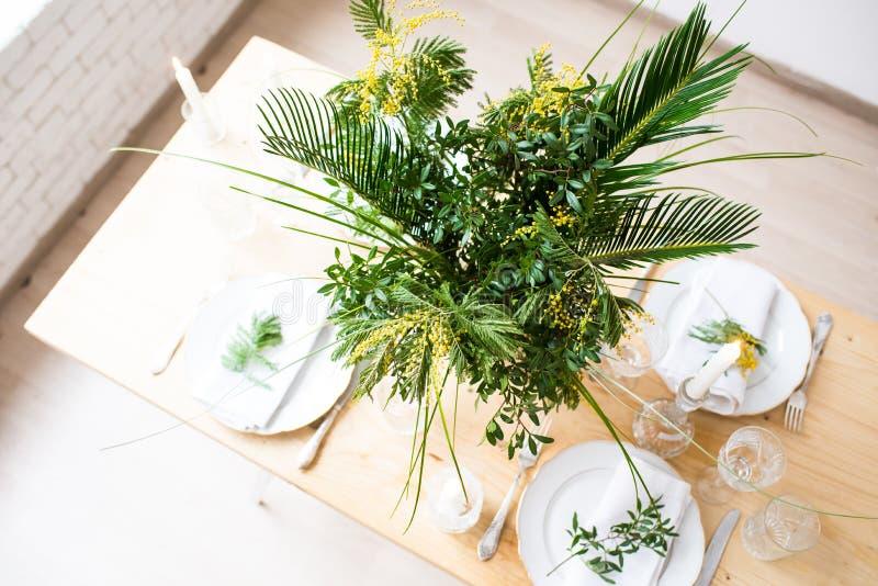 Piękny wiosna stołu położenie z zielenią opuszcza i mimoza rozgałęzia się, jaskrawa bielu stołu gościa restauracji dekoracja obraz royalty free