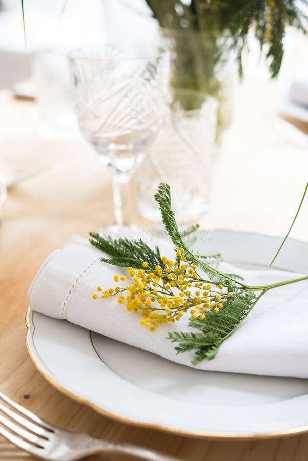 Piękny wiosna stołu położenie z zielenią opuszcza i mimoza rozgałęzia się, jaskrawa bielu stołu gościa restauracji dekoracja obraz stock