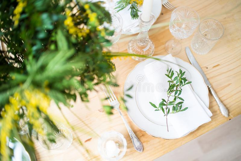 Piękny wiosna stołu położenie z zielenią opuszcza i mimoza rozgałęzia się, jaskrawa bielu stołu gościa restauracji dekoracja obrazy royalty free