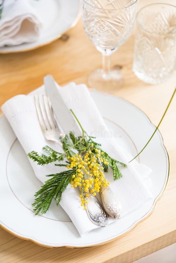 Piękny wiosna stołu położenie z zielenią opuszcza i mimoza rozgałęzia się, jaskrawa bielu stołu gościa restauracji dekoracja zdjęcia stock