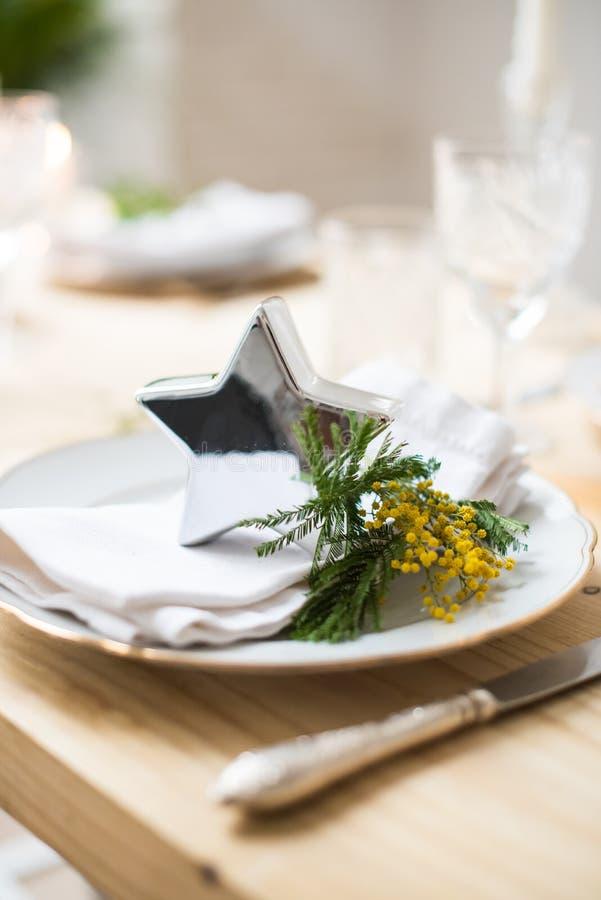 Piękny wiosna stołu położenie z zielenią opuszcza i mimoza rozgałęzia się, jaskrawa bielu stołu gościa restauracji dekoracja obrazy stock