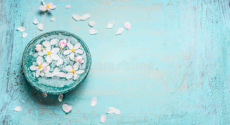 Piękny wiosny okwitnięcie z białymi kwiatami w wodnym pucharze na Turkusowego błękita podławym modnym drewnianym tle, odgórny wid obraz stock