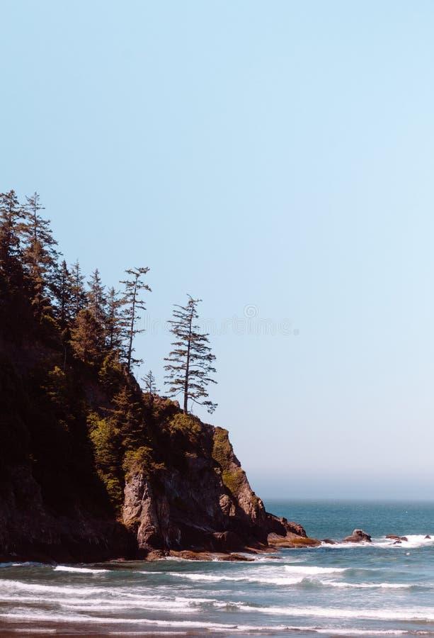 Piękny wybrzeże morze z stromym skalistym wzgórzem z drzewami na lewicie obrazy royalty free
