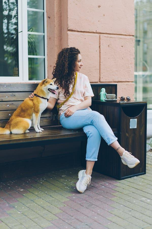 Piękny z włosami dziewczyny obsiadanie w ulicznej kawiarni z śliczny psi ono uśmiecha się fotografia royalty free
