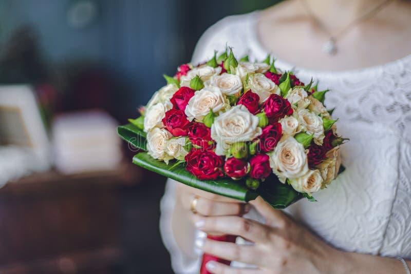 Piękny zadziwiający ślubny bukiet kwiaty panna młoda w biel sukni utrzymuje czerwonych i białych kwiaty fotografia stock