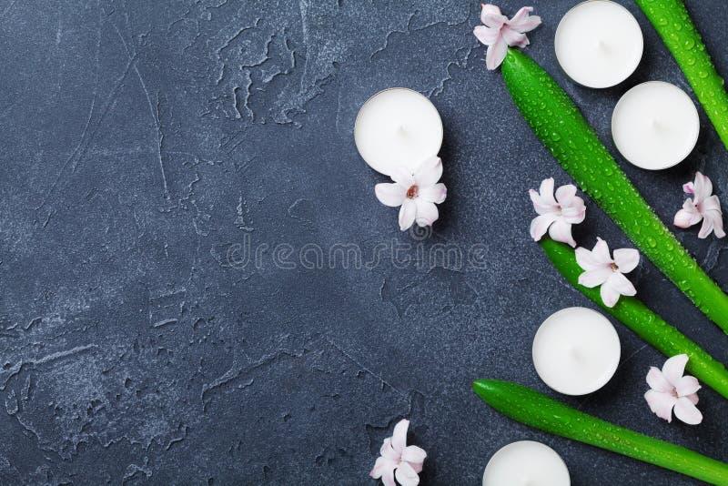 Piękny zdroju tło z liśćmi, kwiatami i świeczkami na czerń kamienia stole od above zieleni, Aromatherapy i piękno zdjęcie stock