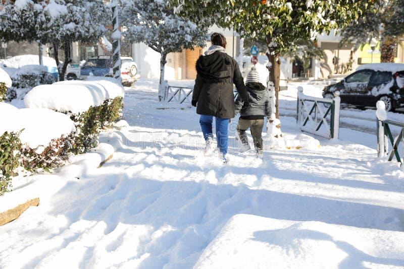 Piękny zima ranek, młoda kobieta z dziecka odprowadzeniem na śnieżystym chodniczku jeden ulica w Ateny i, Grecja obrazy royalty free