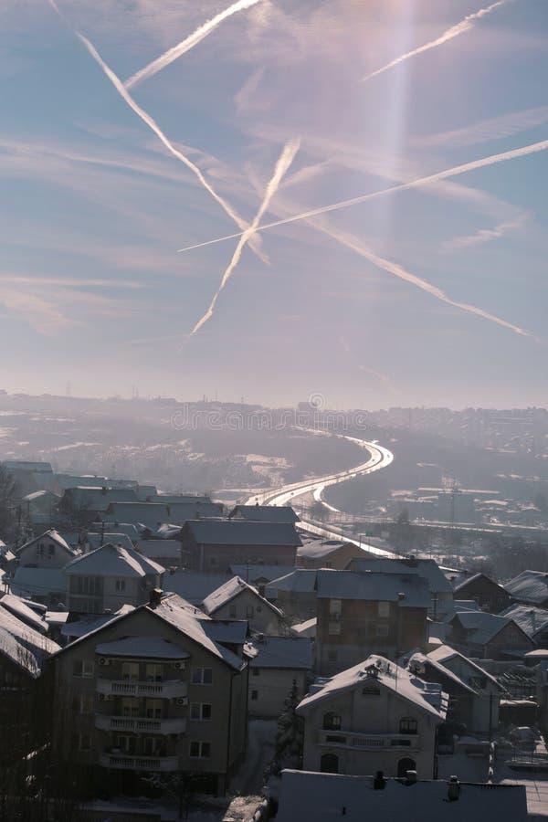 Piękny zima widok domy i budynki z dachami zakrywającymi z ciężkim śniegiem W niebie widzii jest chemtrails fotografia stock