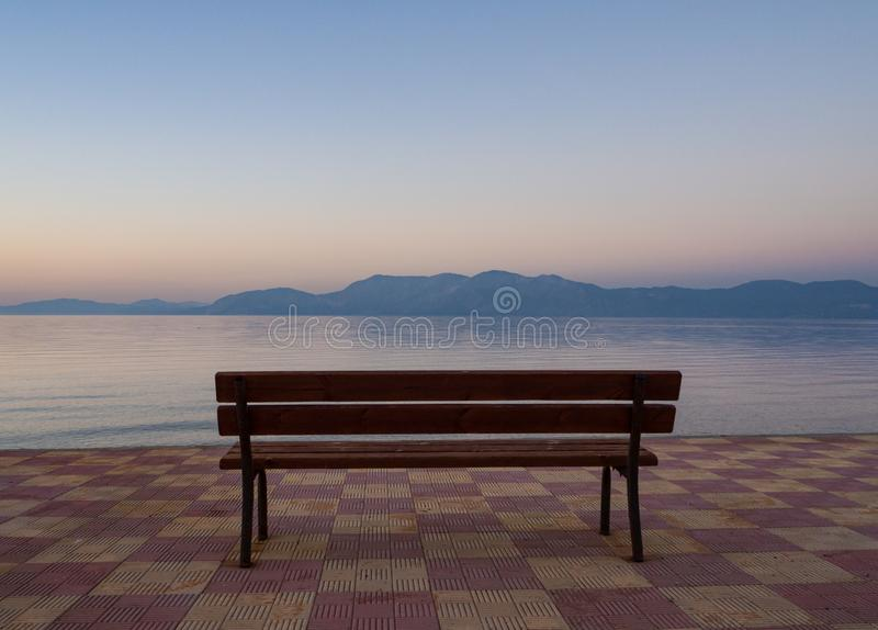 Piękny zmierzch i ławka na nadbrzeżu w Grecja fotografia royalty free