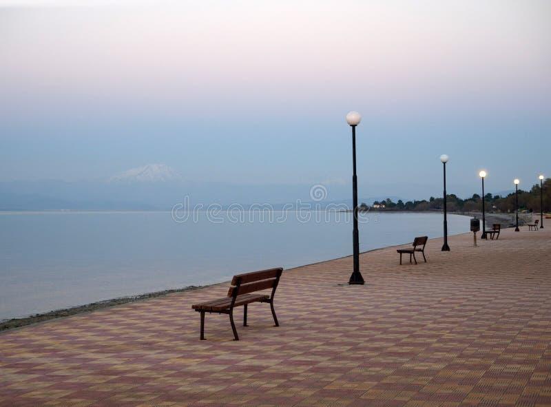 Piękny zmierzch i ławka na nadbrzeżu w Grecja zdjęcia stock