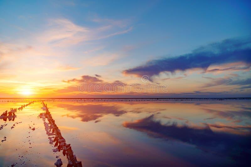 Piękny zmierzch lub wschód słońca nad słonym jeziorem, Drewniany konopie w nagromadzeniu sól po osuszki jezioro zdjęcie stock