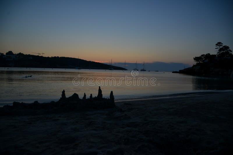 Piękny zmierzch na oceanie z sandcastle w przedpolu zdjęcia stock