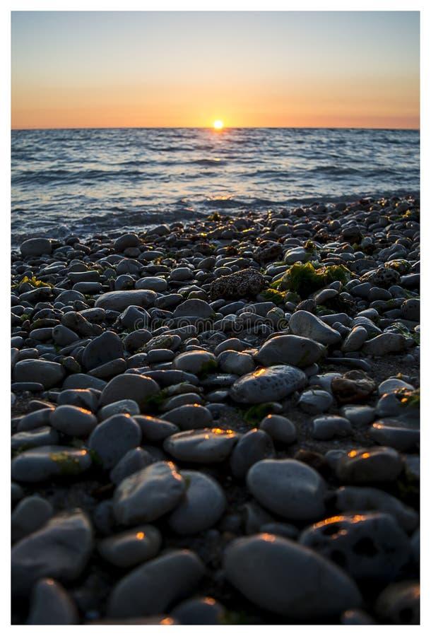 Piękny zmierzch na otoczak plaży fotografia royalty free