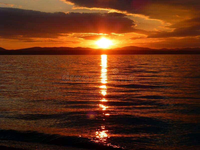 Piękny zmierzch nad jeziorem Czerwony niebo, słońce, chmurnieje i macha zdjęcia royalty free