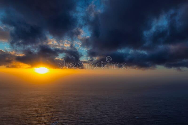 Piękny zmierzch przy oceanem z mgłą na zmroku i horyzoncie chmurnieje fotografia stock