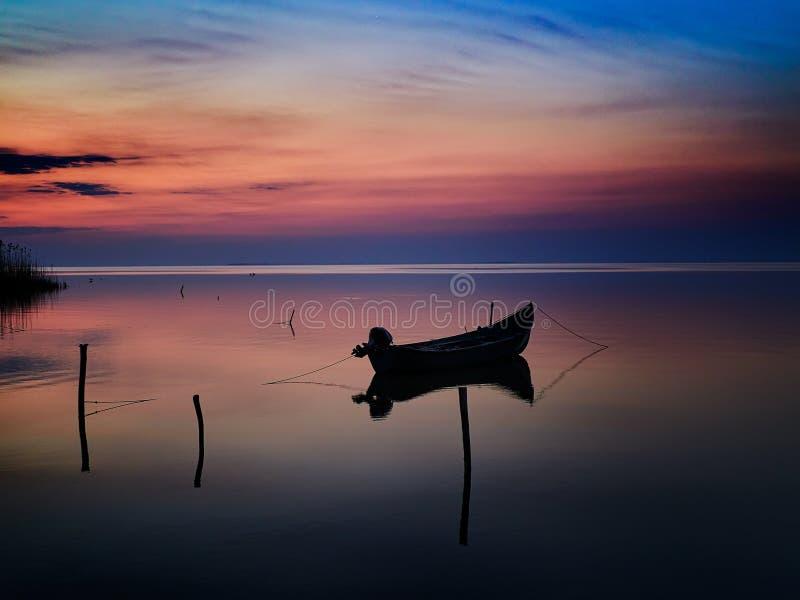 Piękny zmierzch, wschód słońca nad/wodą i sylwetki łodzią rybacką obraz royalty free