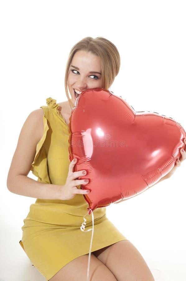 Pięknych kobieta kąsków serca czerwony balon nad białym tłem. zdjęcie royalty free