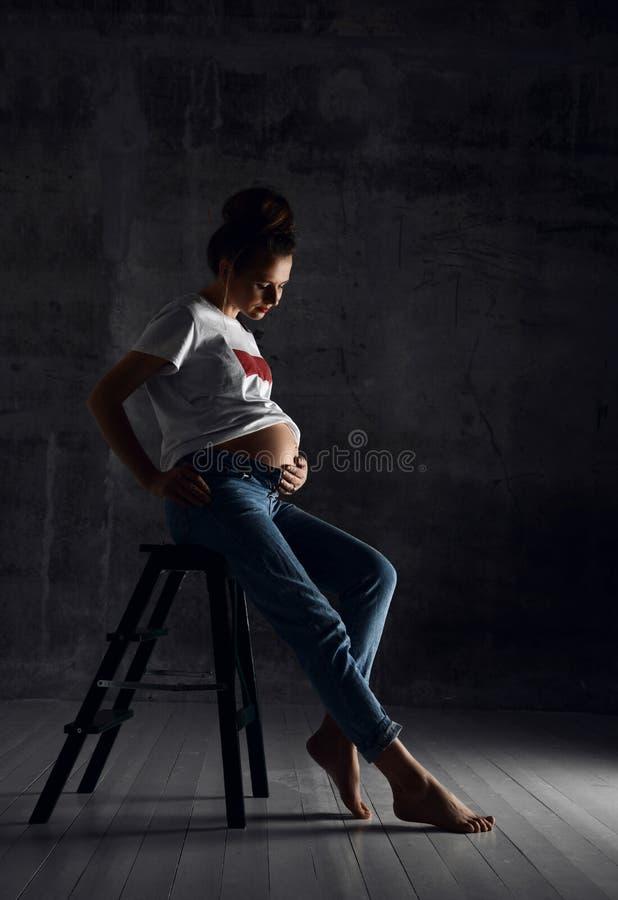 Pięknych potomstw ciężarna szczęśliwa macierzysta kobieta w białej koszulce pozuje na zmroku obraz royalty free