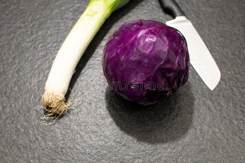 piłka czerwona kapusta, leek i kuchenny nóż na czarnym grań, fotografia stock