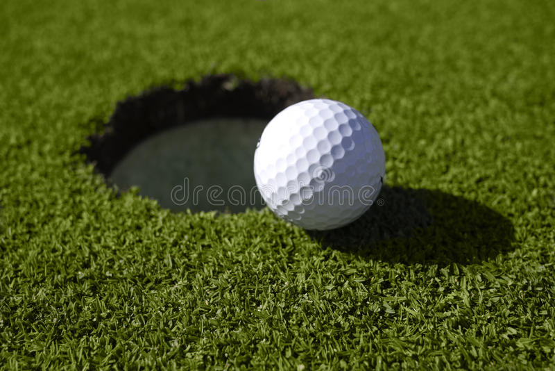 Piłka golfowa siedzi przy krawędzią dziura obraz royalty free