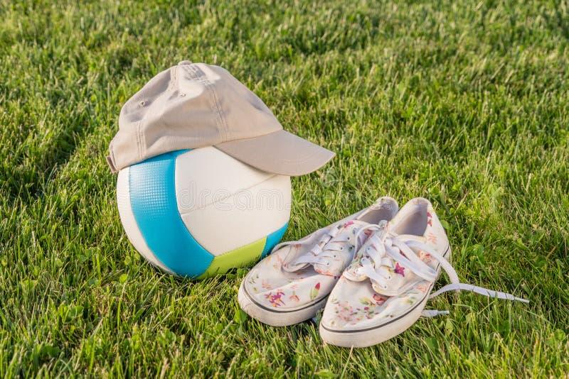 Piłka, nakrętka, buty na trawie fotografia stock