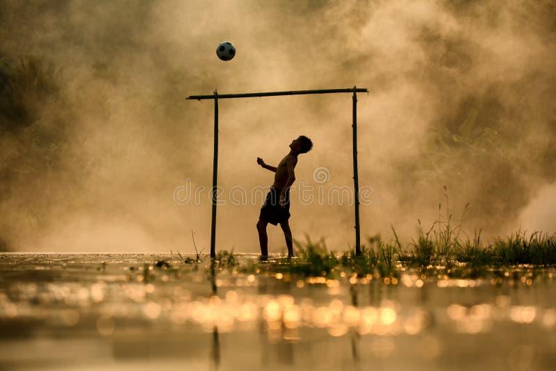 Piłka nożna chłopiec sylwetka bawić się futbol w rzece fotografia stock