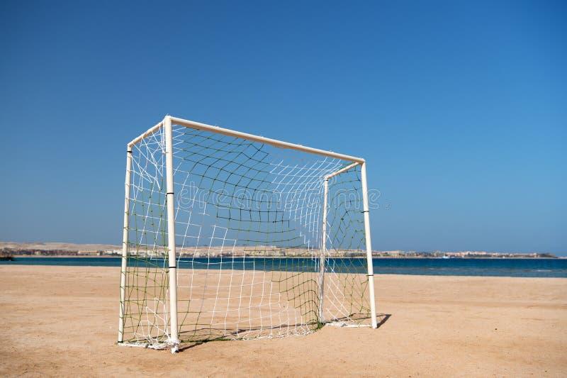 Piłka nożna lub futbolowa brama z siecią na piasek plaży niebieskim niebie i morza krajobrazowym tle Denny kurort rozrywki pojęci zdjęcie stock