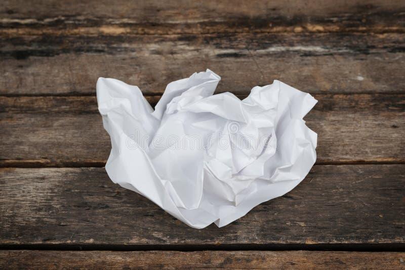 Piłka roztrzaskujący prześcieradło papier nad drewnianym stołem obrazy royalty free
