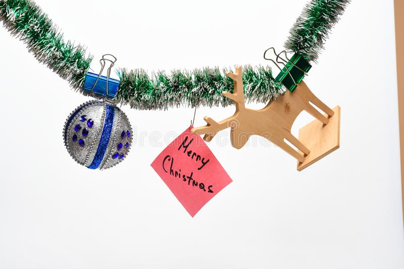 Piłka z ornamentami i drewniana rogacz zabawka wieszamy na migocącym zielonym świecidełku wesoło Bożego Narodzenia pojęcie Świeci zdjęcie stock