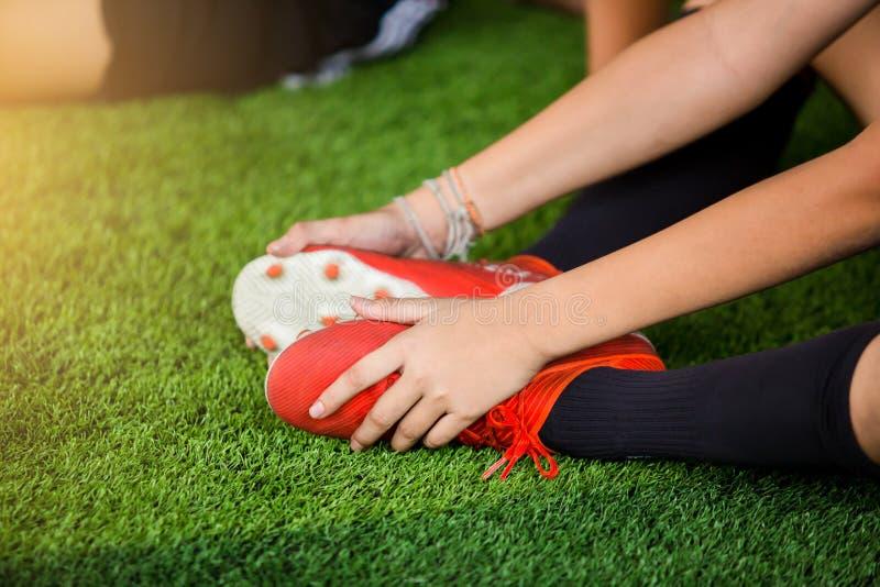 Piłkarz siedzi i łapie kostki stóp z powodu bólu, piłkarz został ranny w nogę zdjęcie stock