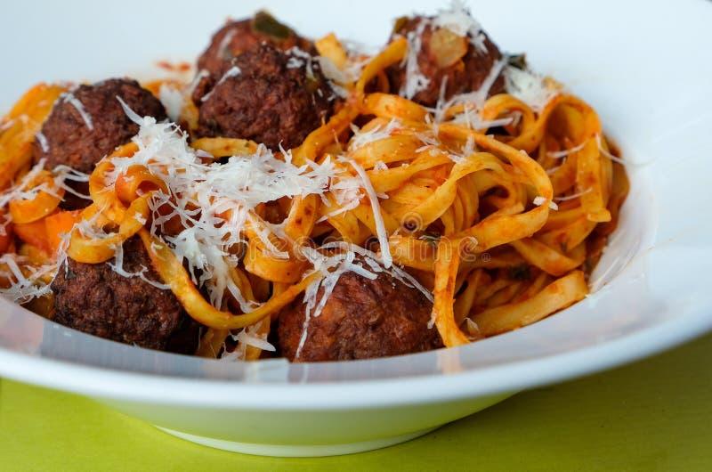 Piłki mięsne z sosem pomidorowym, spaghetti i serem tartym na białym stole, zamknięte obraz stock