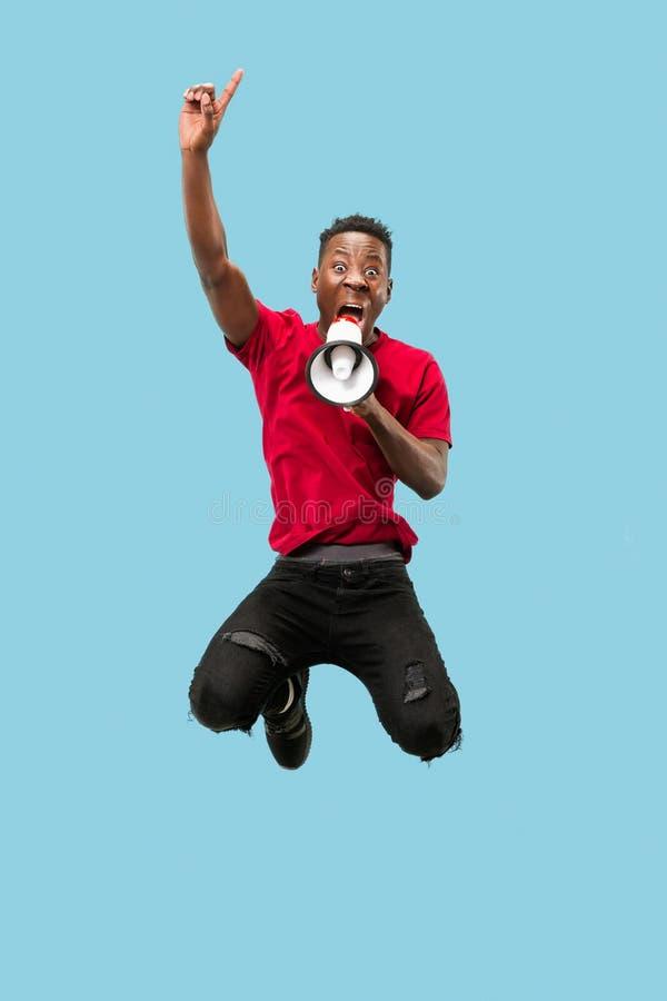 Piłki nożnej fan doskakiwanie na błękitnym tle Młody afro mężczyzna jako fan piłki nożnej z megafonem obrazy stock