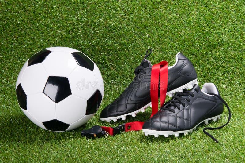 Piłki nożnej piłka, buty i gwizd dla arbitra przeciw tłu trawa, zdjęcie stock
