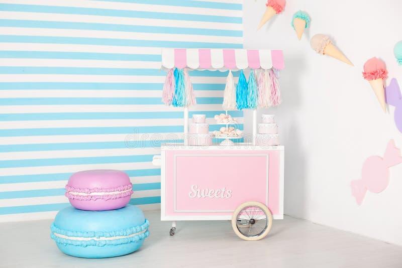 Pi?ce d'enfants avec le fond de rayure bleue zone de photo de stalle de sucrerie avec de grands macarons, bonbons et guimauves ch photos libres de droits