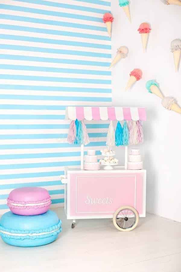 Pi?ce d'enfants avec le fond de rayure bleue zone de photo de stalle de sucrerie avec de grands macarons, bonbons et guimauves ch images libres de droits