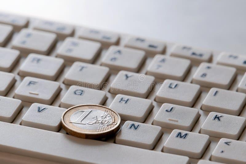 Pi?ce de monnaie dans deux pesos sur le plan rapproch? de clavier d'ordinateur Affaires en ligne en Argentine Ventes internationa photo stock