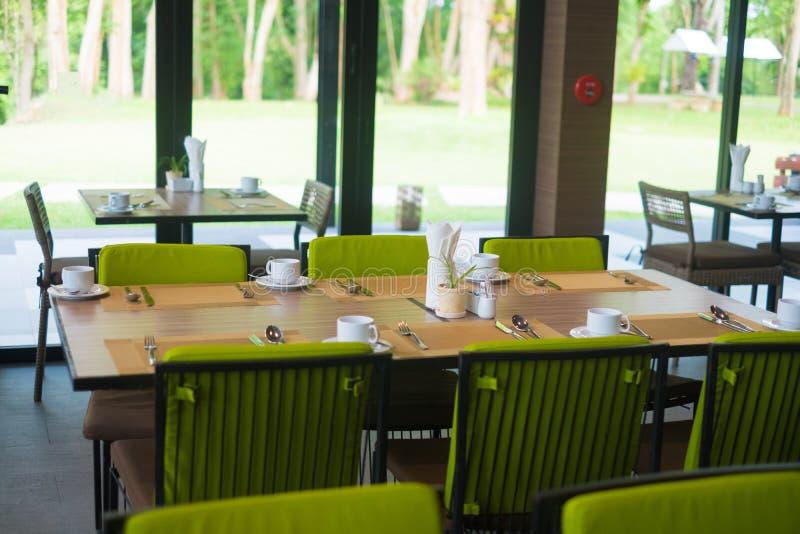 Pi?ce vide de restaurant d'h?tel avec la table et le fauteuil pr?s des fen?tres et de la vue de jardin photographie stock libre de droits