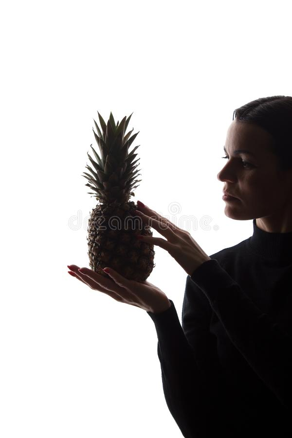Pi?a en las manos del ` un s de la mujer en el fondo blanco fotografía de archivo