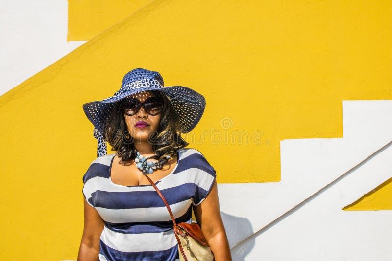 Pi?kna Afryka?ska kobieta w b??kitnej i bia?ej pasiastej smokingowej modelacji przed tradycyjnym bo domem z kolor ? obrazy stock