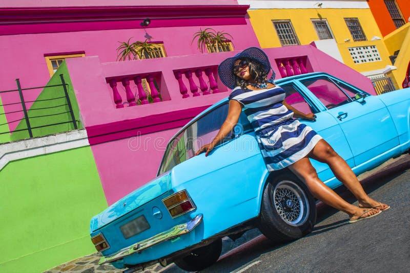 Pi?kna Afryka?ska kobieta w bielu i b??kitnym paskowa? sukni? przed rocznika Ford Cortina tradycyjnymi domami bo i, C obraz stock