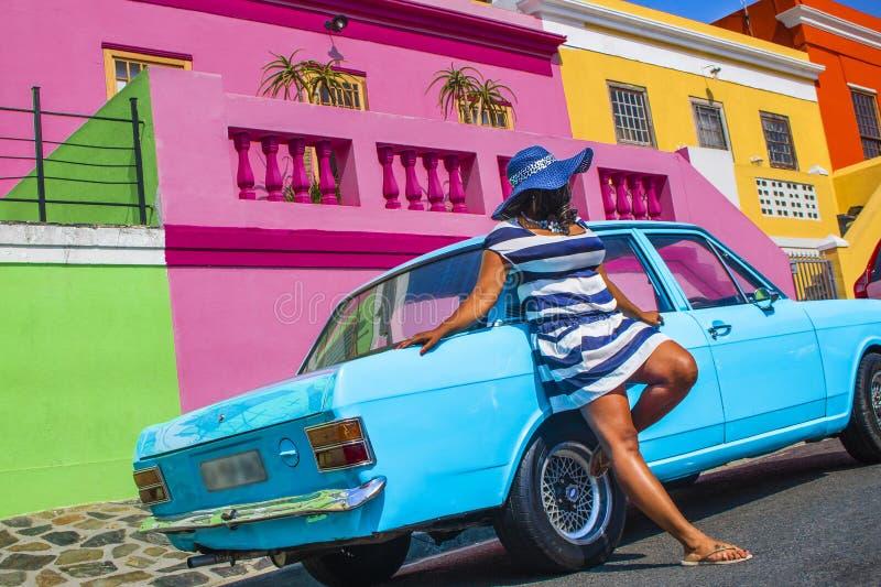 Pi?kna Afryka?ska kobieta w bielu i b??kitnym paskowa? sukni? przed rocznika Ford Cortina tradycyjnymi domami bo i, C obrazy stock