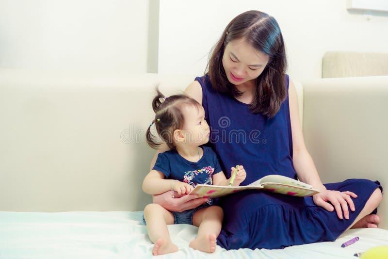 Pi?kna Azjatycka kobieta jest ci??arna Będący ubranym błękitnego smokingowego utrzymanie wpólnie, córka obraz stock