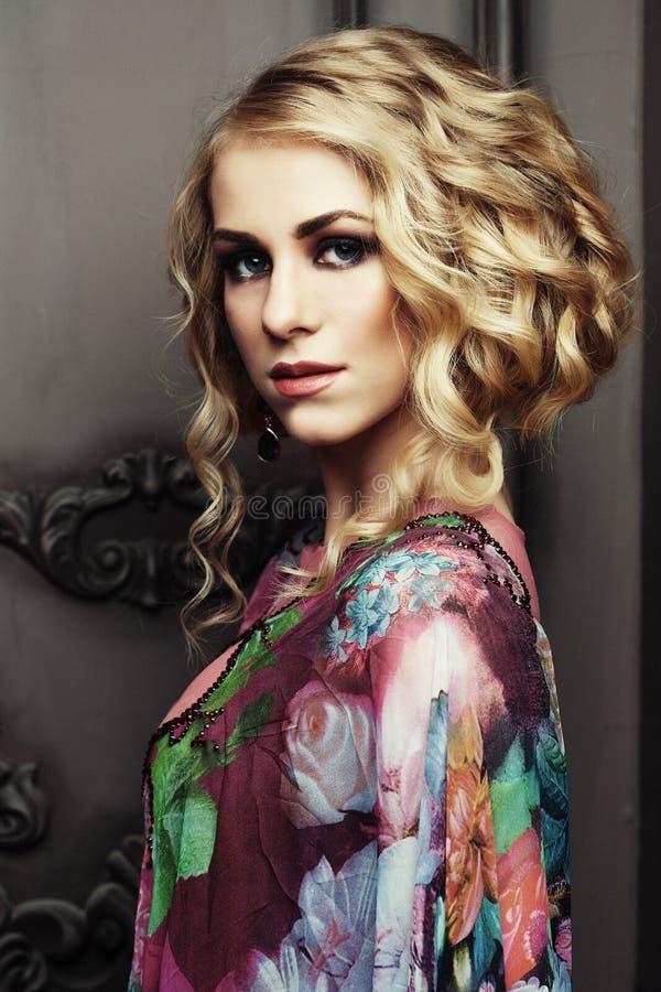 Pi?kna blond kobieta w sukni kwieci?ci kolor?w stojaki w pa?ac zdjęcie royalty free