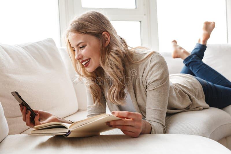 Pi?kna blondynki kobieta pozuje siedzie? indoors w domu u?ywa? telefon kom?rkowego zdjęcie royalty free