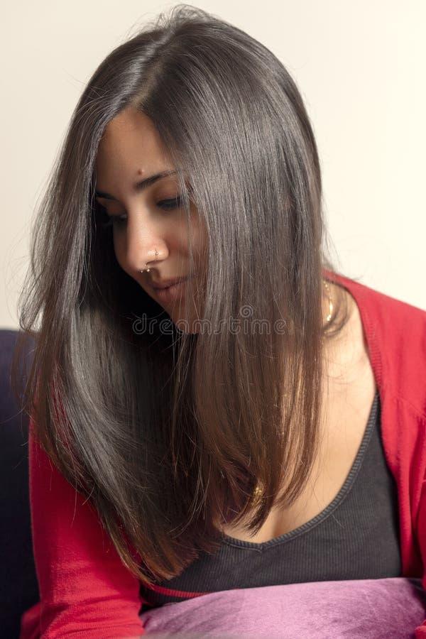 Pi?kna brunetka patrzeje w d?? w odruchowej postawie i zaciszno?ci obraz stock
