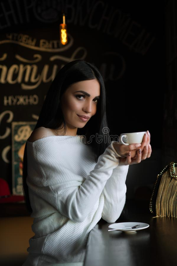 Pi?kna brunetki kobieta w kawiarni z fili?anka kawy fotografia stock